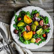 Fresh salad with spinach,arugula and heirloom tomatoes on rustic background