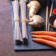 Ingregients for japanese soba stir fry: dry soba noodles, carrots, green pears, red chili, ginger, egg and chop sticks on the slate board