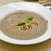 tasty mushroom soup with champignons in white plate on the table