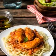 Chicken breasts in tomato and cream sauce with pasta. Rustic style