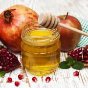 honey  apple and pomegranate on a wooden table