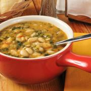 A bowl of healthy kale and white bean soup with dinner rolls