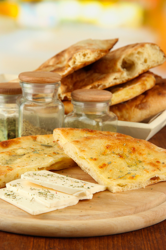 Pita breads with cheese on wooden stand and spice on table on bright background