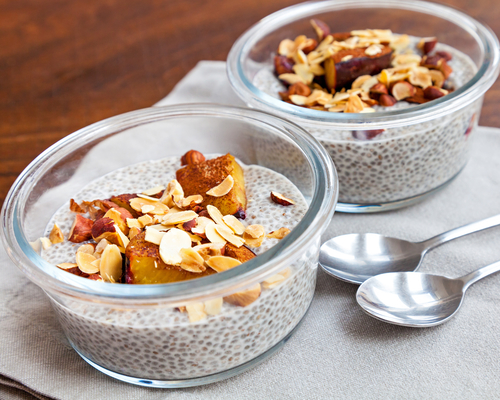 Healthy snack of vanilla chia seed puddings made with coconut milk and topped with oven baked prunes and roasted almonds and hazelnuts. Served in two glass bowls