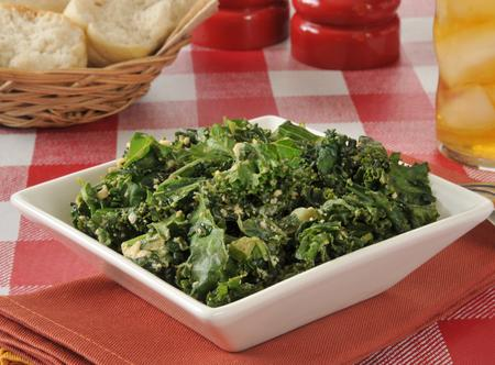Kale salad with iced tea and a basket of dinner rolls