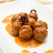 white plate with  beef meatballs and sauce